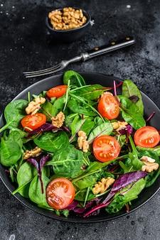 Vegetarische salade met mix bladeren mangold, snijbiet, spinazie, rucola en noten in een slakom. zwarte achtergrond. bovenaanzicht.