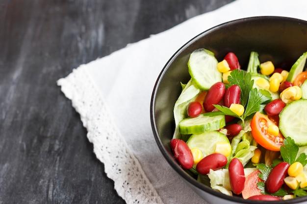 Vegetarische salade met rode mexicaanse bonen, maïs, rucola, kerstomaatjes en olijfolie