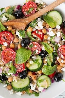 Vegetarische salade quinoa, tomaten, komkommers, kikkererwten, olijven, kruiden, kwark