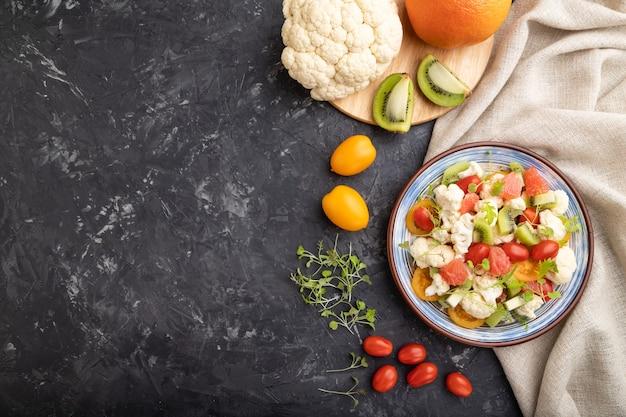 Vegetarische salade van bloemkoolkool, kiwi, tomaten, microgreen spruiten op zwart