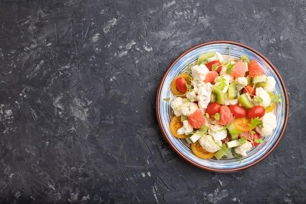 Vegetarische salade van bloemkoolkool, kiwi, tomaten, microgreen spruiten op zwarte betonnen tafel. bovenaanzicht, kopieer ruimte.