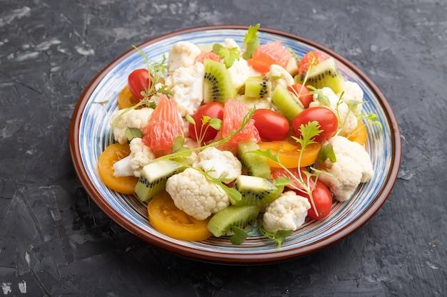 Vegetarische salade van bloemkoolkool, kiwi, tomaten, microgreen spruiten op zwarte betonnen tafel. zijaanzicht, close-up.