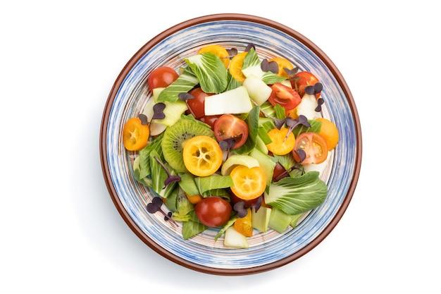 Vegetarische salade van pac choi kool, kiwi, tomaten, kumquat, microgreen spruiten geïsoleerd op een witte ondergrond