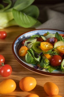 Vegetarische salade van pac choi kool, kiwi, tomaten, kumquat, microgreen spruiten op een houten achtergrond en linnen textiel. hard licht, contrast.