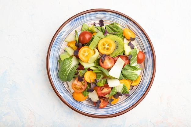 Vegetarische salade van pac choi kool, kiwi, tomaten, kumquat, microgreen spruitjes op een witte betonnen ondergrond