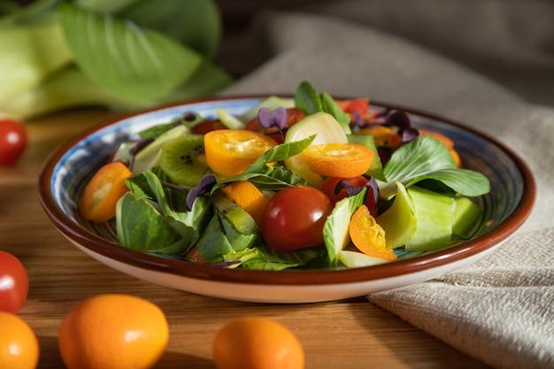 Vegetarische salade van pac choi kool, kiwi, tomaten, kumquat, microgroene spruiten op een houten oppervlak. het zijaanzicht, sluit omhoog, harde lichte, selectieve nadruk.
