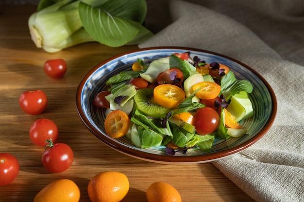 Vegetarische salade van pac choi kool, kiwi, tomaten, kumquat, microgroene spruiten op een houten oppervlak. zijaanzicht, close-up, hard licht.