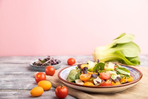 Vegetarische salade van pac choi kool, kiwi, tomaten, kumquat, microgroene spruiten op grijs en roze oppervlak en linnen textiel