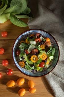 Vegetarische salade van pac choi kool, kiwi, tomaten, kumquat, microgroene spruitjes