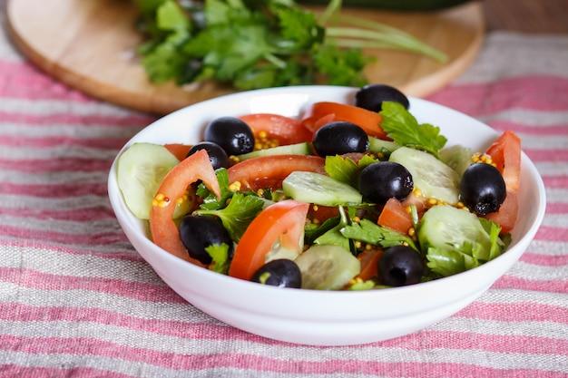 Vegetarische salade van tomaten, komkommers, peterselie, olijven en mosterd op linnen tafelkleed.