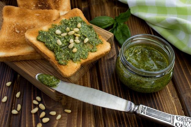 Vegetarische sandwiches met pesto saus en pijnboompitten op de houten snijplank
