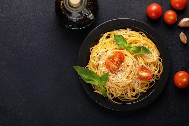 Vegetarische smakelijke klassieke italiaanse spaghetti pasta met basilicum, tomatensaus, kaas parmezaanse kaas en olijfolie op zwarte plaat op donkere tafel. bovenaanzicht, horizontaal. kopieer ruimte voor uw tekst.