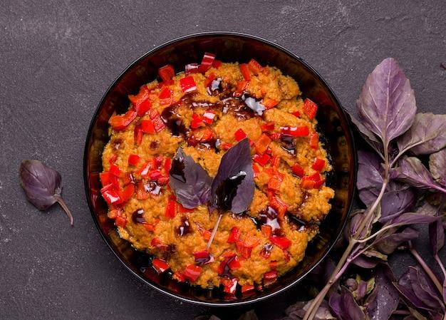 Vegetarische soja vleesgerecht met basilicum en peper op een zwarte achtergrond.