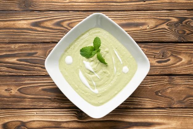 Vegetarische spinaziesoep met yoghurt en muntblaadjes in een witte keramische plaat