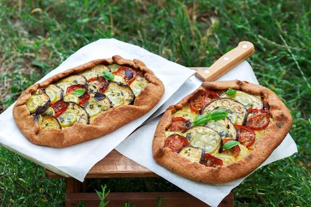 Vegetarische taarten met groenten en kruiden op een krukje tegen een achtergrond van groen gras.