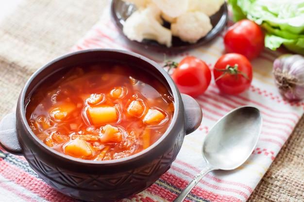 Vegetarische tomatensoep met kool en bloemkool in een keramische rustieke kom