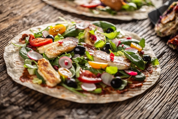 Vegetarische tortilla met open bovenkant met salade, radijs, cherrytomaatjes, olijven, granaatappel en gegrilde haloumi-kaas.