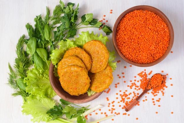 Vegetarische vleesloze gehaktballen gemaakt van linzen en wortelen in een houten plaat met groenten en groenen.