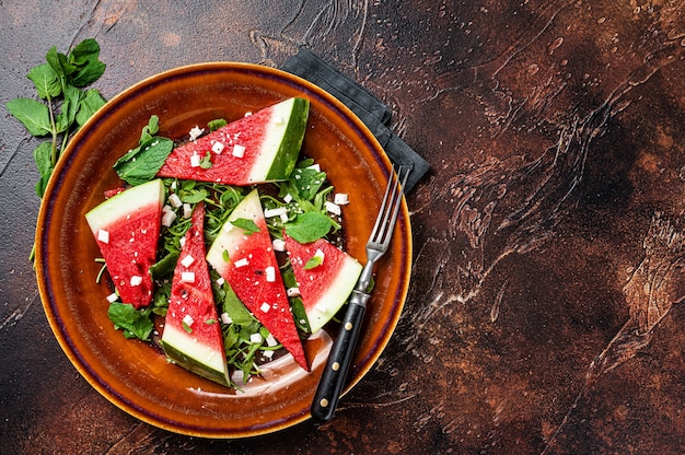 Vegetarische watermeloensalade met fetakaas, rucola, uien. donkere achtergrond. bovenaanzicht. ruimte kopiëren.