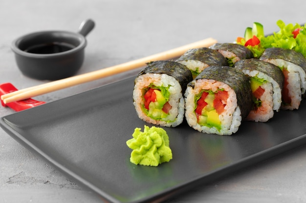Vegeterian sushi roll met groenten op stenen plaat close-up