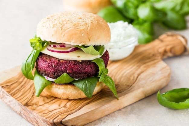 Veggie bietenburgers met groenten en griekse saus.