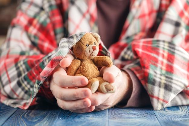 Veilig concept voor kind, mannelijke hand houden speelgoed beer