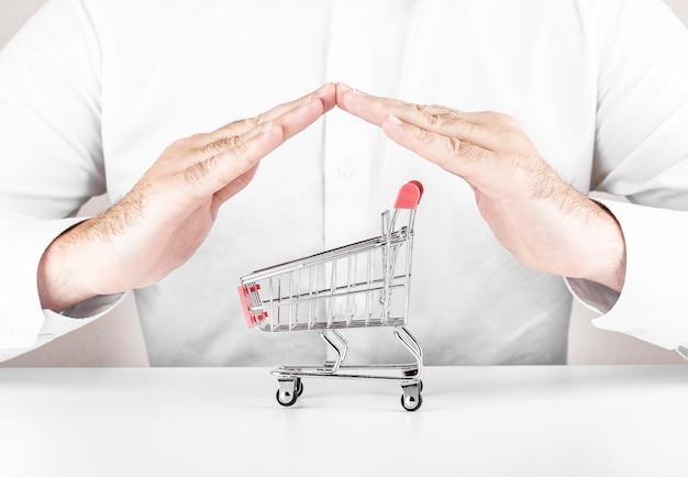 Veilig online winkelconcept. boodschappenwagentje dat met hand op wit wordt beschermd