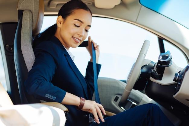 Veilig rijden. positieve jonge vrouw die lacht tijdens het controleren van haar veiligheidsgordel