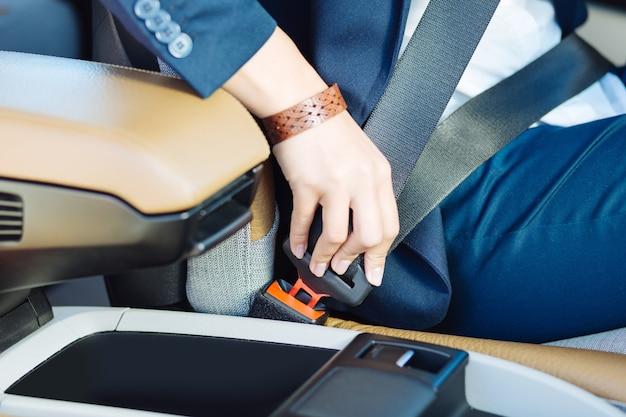 Veilig rijden. sluit omhoog van een veiligheidsgordel die door een professionele vrouwelijke bestuurder wordt vastgemaakt