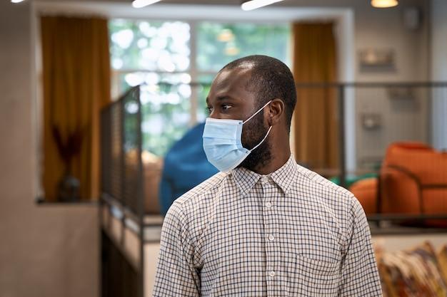 Veilig werken tijdens coronavirus portret van jonge afro-amerikaanse man mannelijke kantoormedewerker die draagt