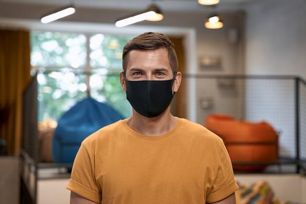 Veilig werken tijdens coronavirus portret van jonge man mannelijke kantoormedewerker die zwarte beschermende draagt
