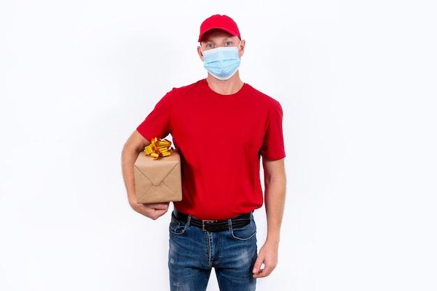 Veilige bezorging van cadeaus voor feestdagen. een koerier in rood uniform en beschermend medisch masker houdt doos met een boog vast. contactloze bestellingen van geschenken op afstand in quarantaine tijdens de coronaviruspandemie.