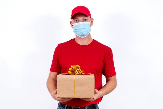 Veilige bezorging van cadeaus voor feestdagen. een koerier in rood uniform en beschermend medisch masker houdt doos met een boog vast.