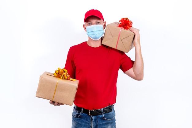 Veilige, contactloze bezorging van vakantiegeschenken op afstand tijdens de coronaviruspandemie. een koerier in een