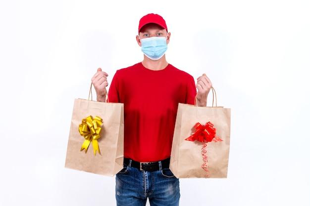 Veilige, contactloze bezorging van vakantiegeschenken op afstand tijdens een coronaviruspandemie. een koerier in het rood