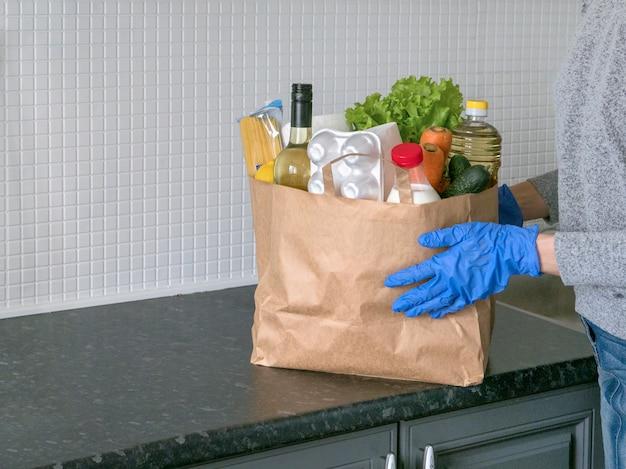 Veilige levering aan huis. een pakket met producten als melk, eieren, groenten en wijn in een moderne keuken