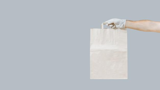 Veilige levering aan huis in een pandemie. coronavirus 2019-ncov-bescherming. koerier de papieren zak dient medische handschoen in.