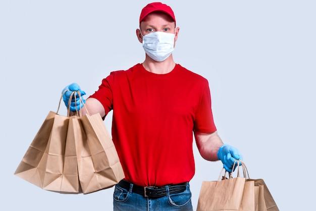 Veilige levering. een koerier in een rood uniform en een beschermend masker en handschoenen heeft een grote bestelling, veel papieren zakken, contactloos bezorgvoedsel in quarantaine. donatie van vrijwilligers. zero waste.