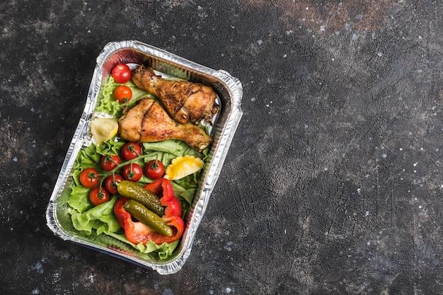 Veilige levering van kant-en-klaar voedsel in folie. kippenboutjes met verse groenten en gepekelde komkommers met de pompoen