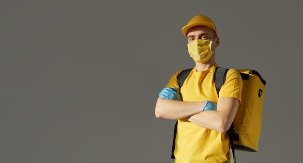 Veilige voedselbezorging. koerier in geel uniform, beschermend masker en handschoenen levert afhaalmaaltijden tijdens quarantaine van coronovirus. kopieer ruimte voor tekst