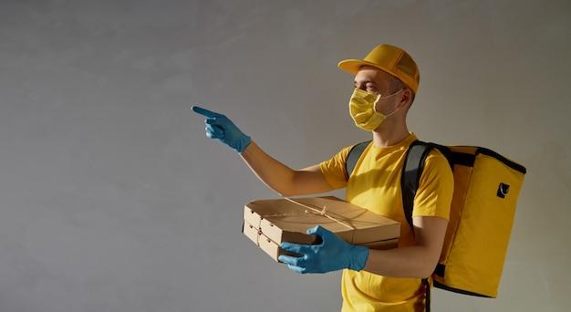 Veilige voedselbezorging. koerier in geel uniform, beschermend masker en handschoenen levert afhaalmaaltijden tijdens quarantaine van coronovirus. wijzend naar links.
