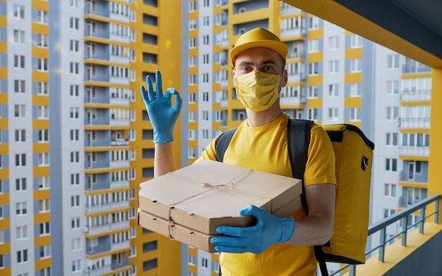 Veilige voedselbezorging. koerier in geel uniform, beschermend masker en handschoenen levert afhaalmaaltijden tijdens quarantaine van coronovirus