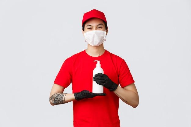 Veiligheid contactloze levering, vervoerders concept. koerier in medisch masker, handschoenen en rood uniform, met handdesinfecterend middel, suggereert dat klanten veilig thuis blijven terwijl ze pakketten bezorgen tijdens covid 19