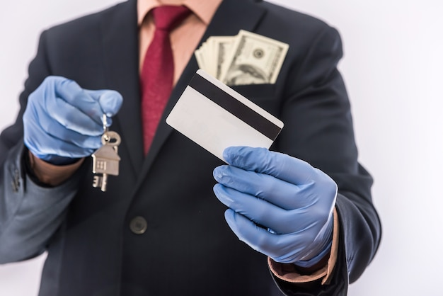 Veiligheid koop of huur huis man in medische handschoenen houden huissleutel en dollar. ncov-2019