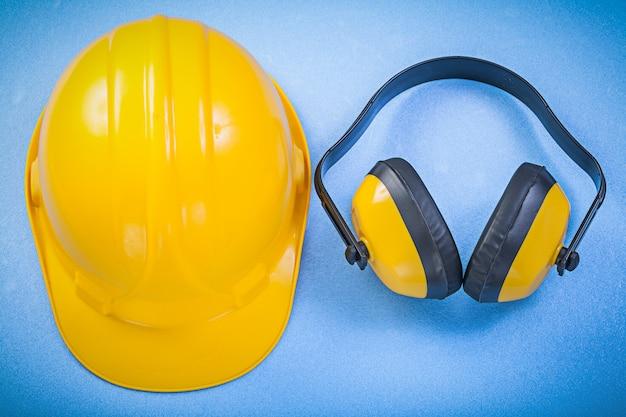Veiligheid oorkappen en bouwvakker op blauw oppervlak