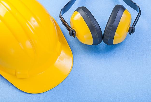 Veiligheid oorkappen en helm bouwen op blauw oppervlak