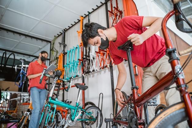 Veiligheid op het werk een verkoper en een verkoopster met masker bereiden en controleren fietsonderdelen