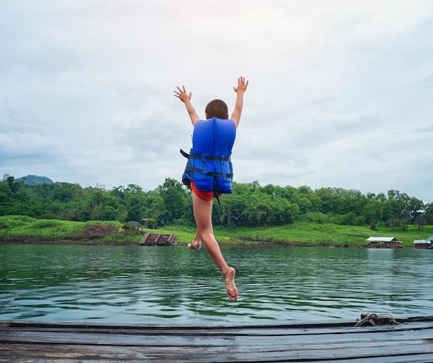 Veiligheid van leven concept. kleine blanke jongen gebruikt een reddingsvest, springt van een houten in water.