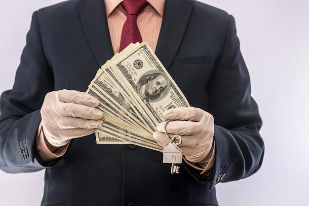 Veiligheid verkoop of huur huis man in medische handschoenen houden huissleutel en dollar. ncov-2019
