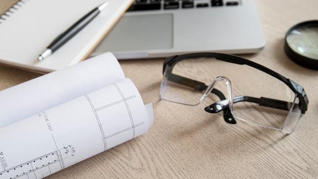 Veiligheidsbril en blauwdruk dichtbij laptop en notitieboekje